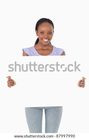 Close up of smiling woman presenting placeholder on white background - stock photo