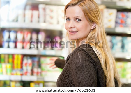 Close-up of smiling woman reaching for products arranged in refrigerator and looking at camera - stock photo