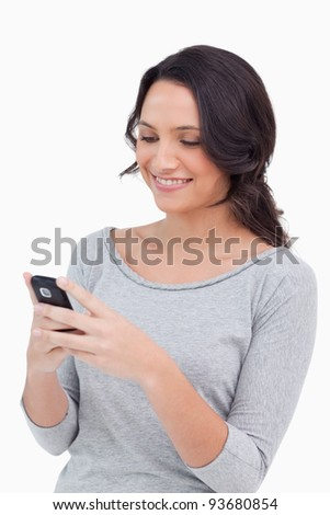 Close up of smiling woman reading text message against a white background - stock photo
