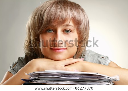 Close-up of smiling woman with chin resting on hands isolated on grey - stock photo
