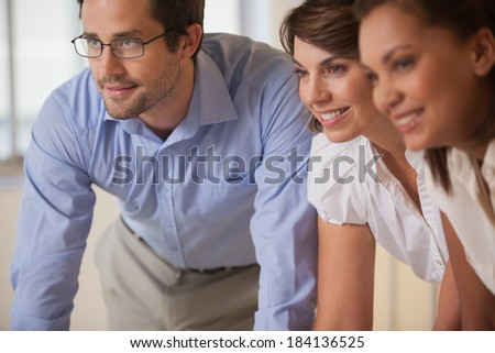 Close-up of smiling young business people looking away at office - stock photo