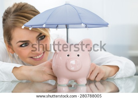 Close-up Of Smiling Young Businesswoman Sheltering Piggybank With Umbrella On Desk - stock photo