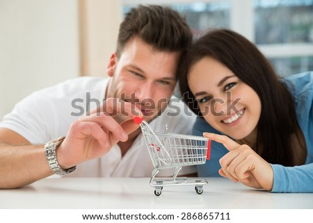 Close-up Of Smiling Young Couple With Miniature Empty Shopping Cart - stock photo