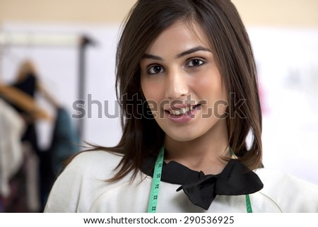 Close-up of smiling young female fashion designer in clothing store - stock photo