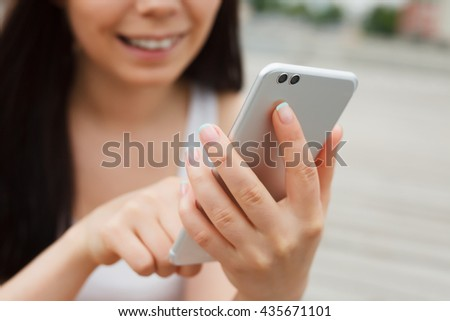 Close up of smiling young girl using huge tablet smartphone with dual rear camera with a happy smile. Modern technology, cute model - stock photo