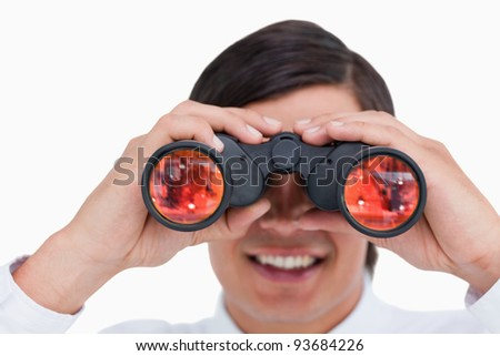 Close up of smiling young tradesman looking through binoculars against a white background - stock photo