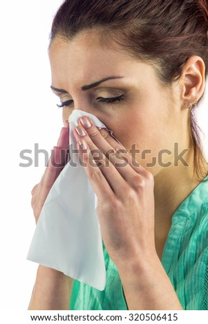 Close-up of sneezing woman with eyes closed and tissue on mouth against white background
