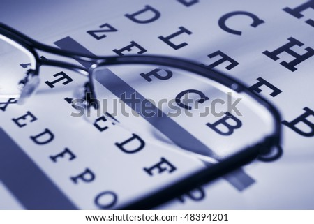 Close up of Snellen chart and spectacles differential focus blue tone - stock photo