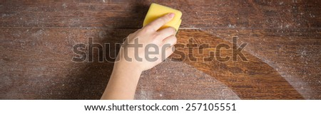Close-up of soiled wooden parquet cleaning with dishrag - stock photo
