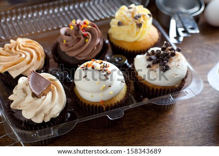 Close up of some decadent gourmet cupcakes frosted with a variety of frosting flavors. Shallow depth of field. - stock photo