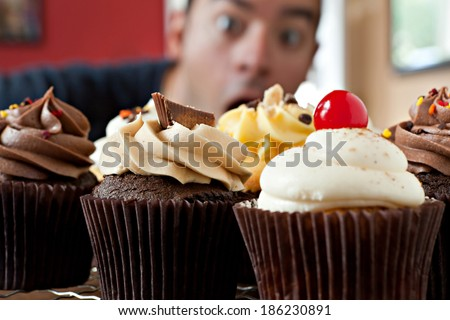 Close up of some delicious gourmet cupcakes frosted with a variety of frosting flavors.  Shallow depth of field with the face of a hungry man lurking in the background.