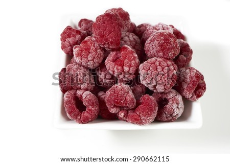 Close up of some frozen raspberries in a white porcelain dish on a white background - stock photo