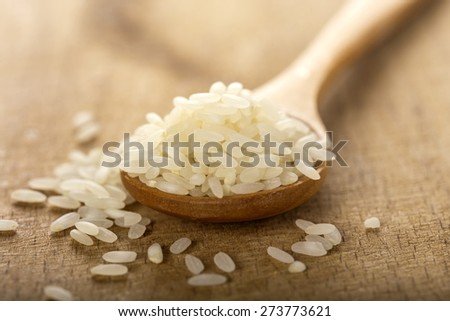 Close up of some rice in wooden spoon on wood background - stock photo
