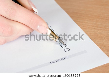 Close up of someone's hand filling in a checklist. - stock photo