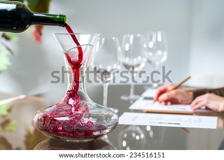 Close up of Sommelier pouring red wine into decanter at wine tasting session. - stock photo