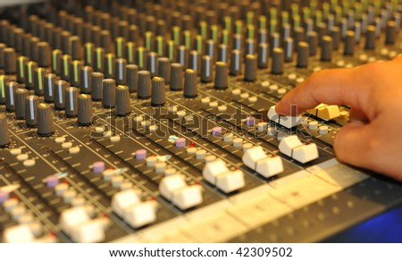 Close-up of sound engineer's hand moving sliders on audio mixing board - stock photo