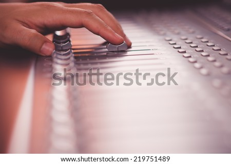 Close-up of sound engineer working on music mixer in the recording studio - stock photo