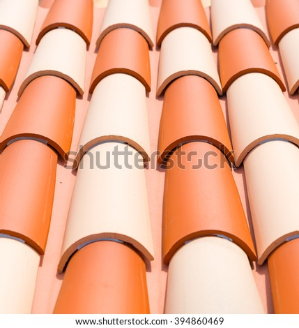 Close up of spanish style clay roof tiles.  Close up of attractive spanish style terra cotta roof tiles placed in neat rows on a slant, image for construction industry concept, business blog website - stock photo