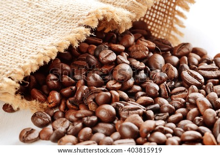 Close-up of spilled coffee beans from canvas sack - stock photo