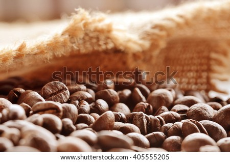 Close-up of spilled coffee beans from canvas sack. Beautiful brown quality coffee beans close-up view on desk. - stock photo