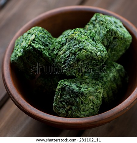 Close-up of spinach cubes in a ceramic bowl, studio shot - stock photo