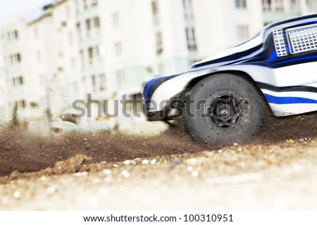Close up of spinnig wheel of quickly going radio controlled car - stock photo
