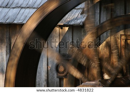 Close-Up of Spinning Grist Mill Waterwheel with Motion Blur - stock photo