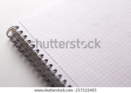 close up of spiral note book with checked pages - stock photo