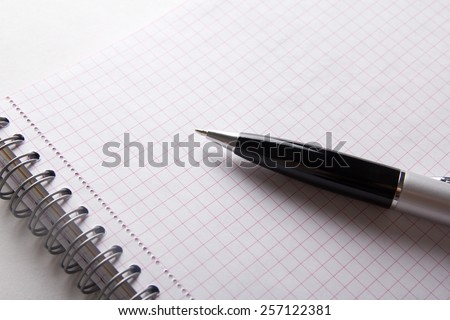 close up of spiral note book with checked pages and pen - stock photo
