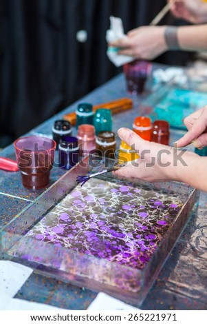 Close up of splashing paint over water surface, marbling - stock photo
