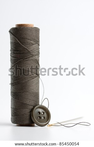 Close-up of spool of thread and button - stock photo