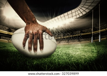 Close-up of sports player holding ball against rugby pitch - stock photo