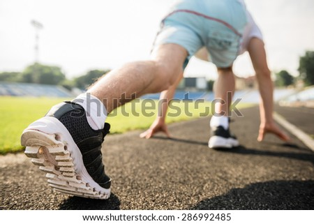 Close-up of sporty man ready to run sprint. Male athlete in powerful starting line pose.
