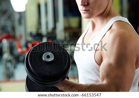 Close-up of sporty man training in gym with barbell - stock photo