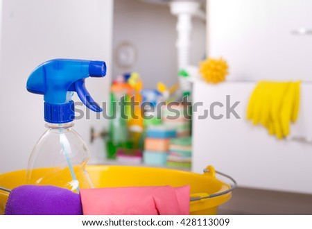 Close up of spray bottle and cloths in bucket. Cleaning supplies and equipment stored in kitchen cabinet in background