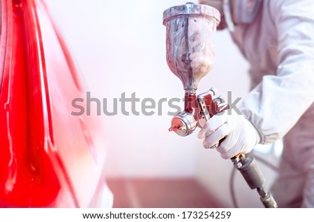 Close-up of spray gun with red paint painting a car in special booth - stock photo