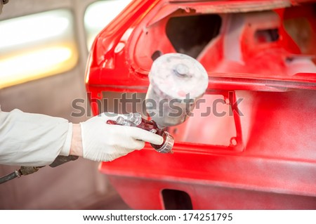 Close-up of spray paint gun painting a red car in painting booth - stock photo