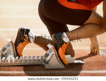 Close-up of sprinter feet in starting block - stock photo