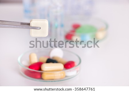 Close up of square shaped pill holding by tweezers above petri dish with different drugs - stock photo