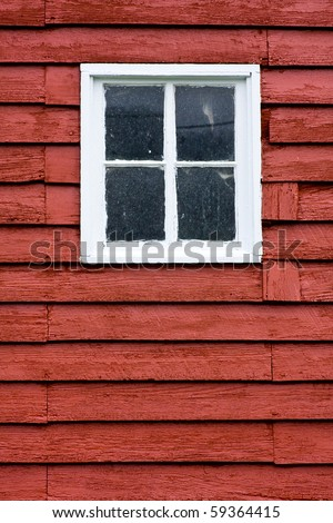 Close up of square white window in old red wooden barn wall. - stock photo