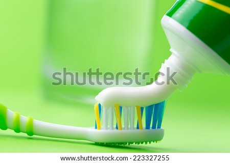 Close up of squeezing toothpaste on toothbrush on green background - stock photo