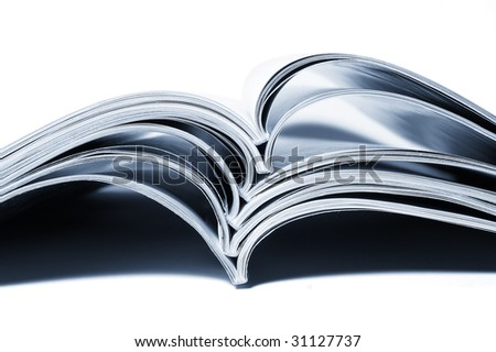 close up of stack of magazines on white background