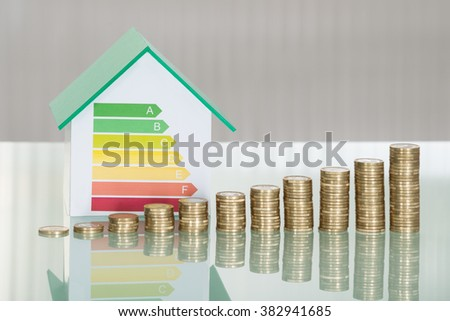Close-up Of Stacked Coins And House Model Showing Energy Efficiency Rate On Desk