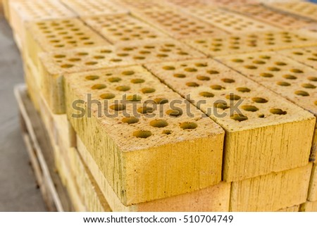 Close up of stacked yellow holed bricks.