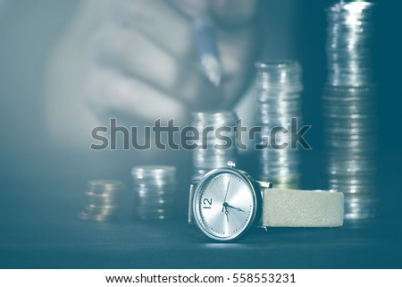 Close up of stacking coins with watch,focus of watch