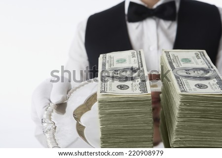 Close up of stacks of money on silver platter - stock photo