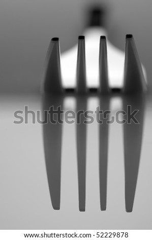 Close-up of stainless fork on light background with shadows. B&W. Selective focus on top of prongs. - stock photo