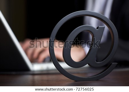 Close up of stand-alone at symbol with businessman in background in dark suit sitting at office desk working on laptop using the internet, low-key image. - stock photo
