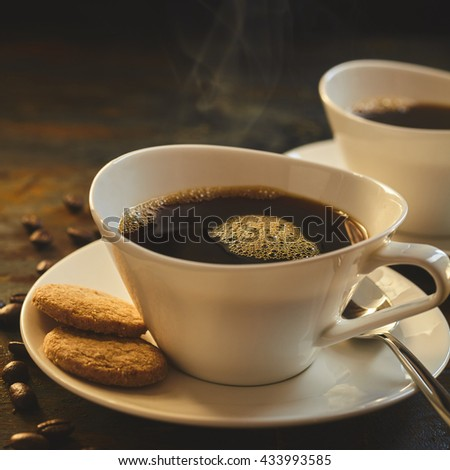 Close up of steaming hot coffee served in porcelain cups besides tasty cookies and loose beans - stock photo