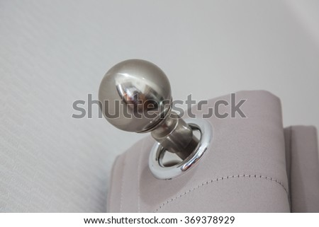 close up of steel knob and Gray colored curtains